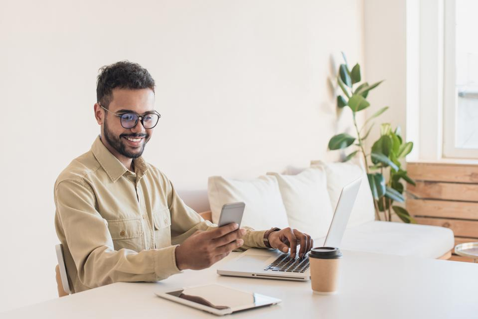 Young man professional using laptop working at home online