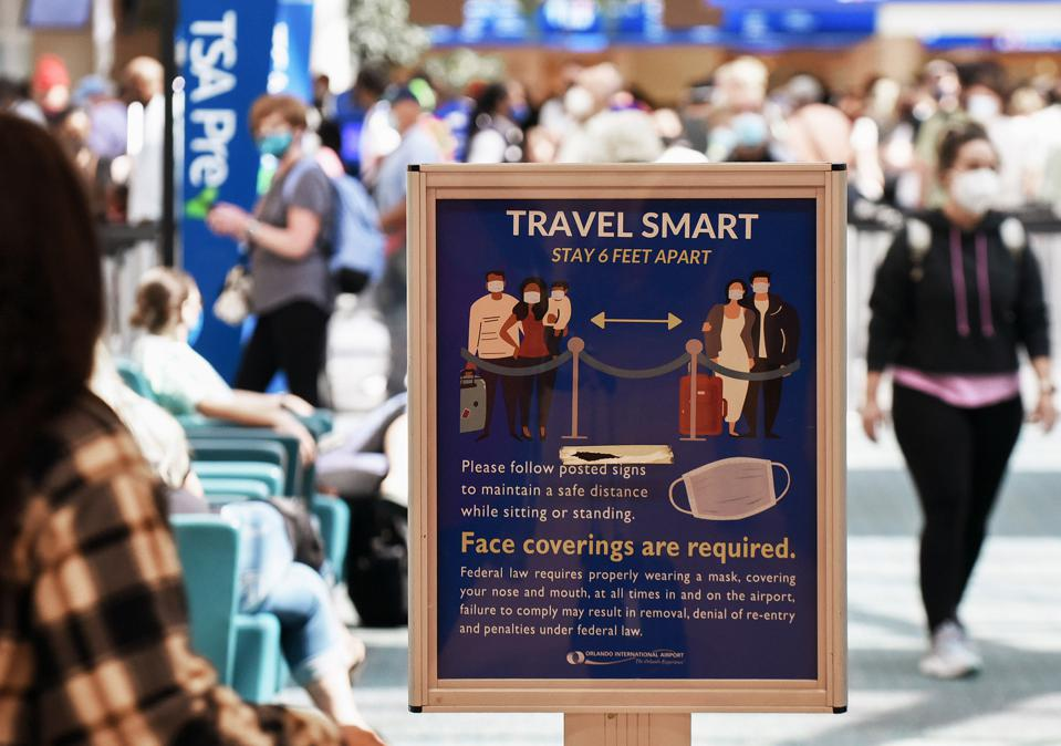 A sign advising travelers of the requirements for social...