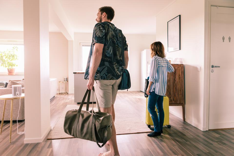 Couple walking with luggage in apartment during staycation