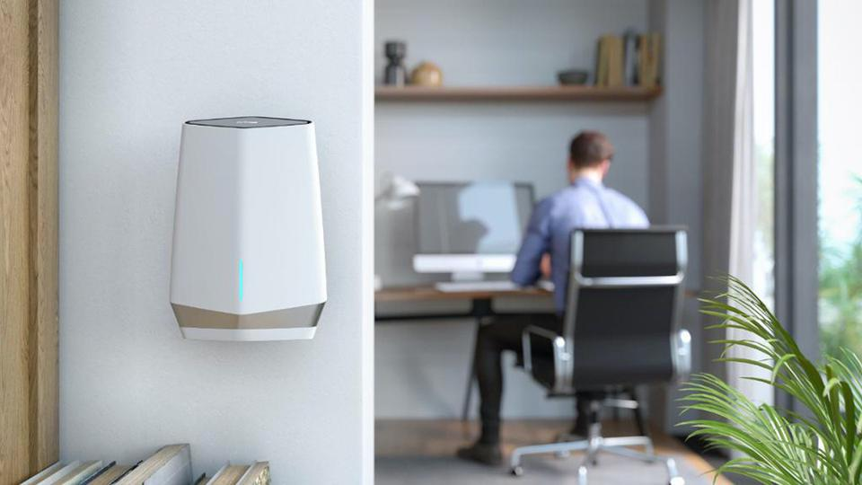 Man sitting at desk with a Netgear Orbi Pro WiFi 6 Mini Mesh satellite in the foreground