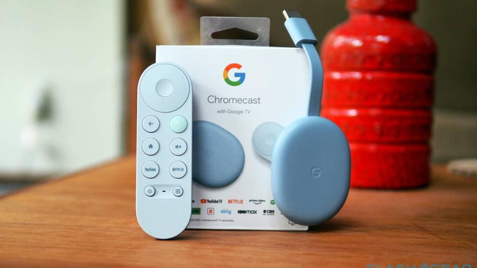 Picture of a Google TV dongle and remote in front of the product's box