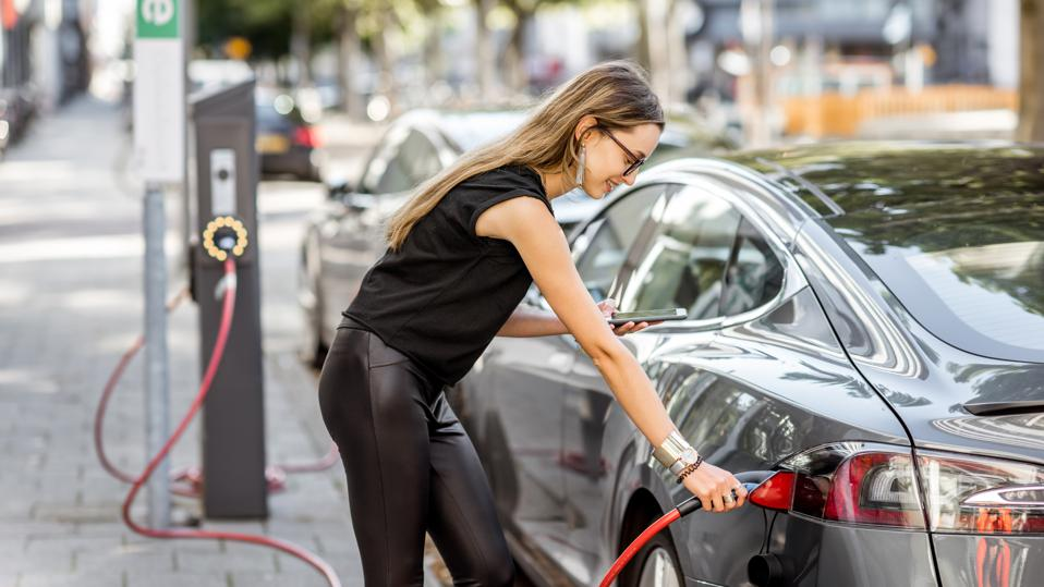 Young woman in black clothes putting connector into the electric car outdoors on the street in Rotterdam