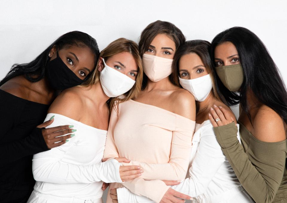 A group of women pose together with MTAM masks on,