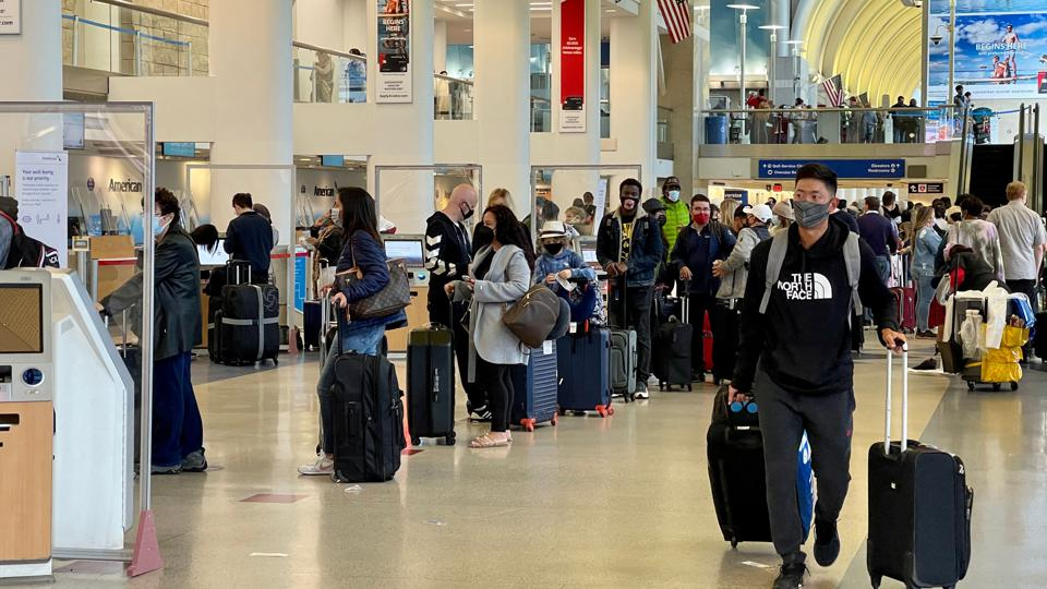 Travelers with masks wait in line Los Angeles airport