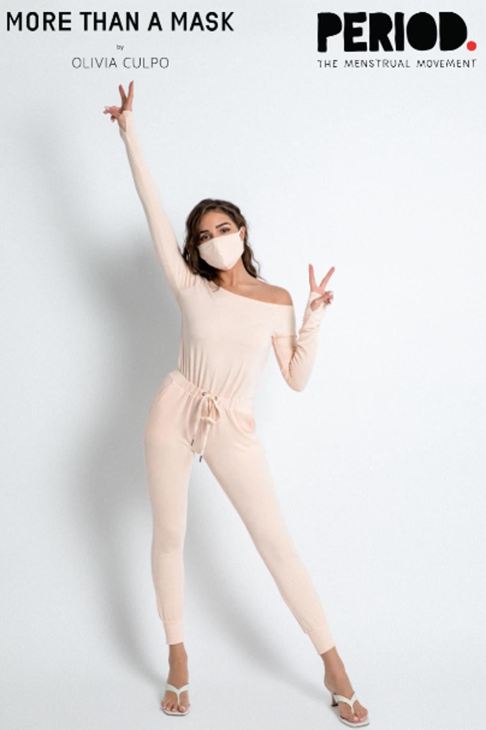 Olivia Culpo poses with a pink jump-suit on