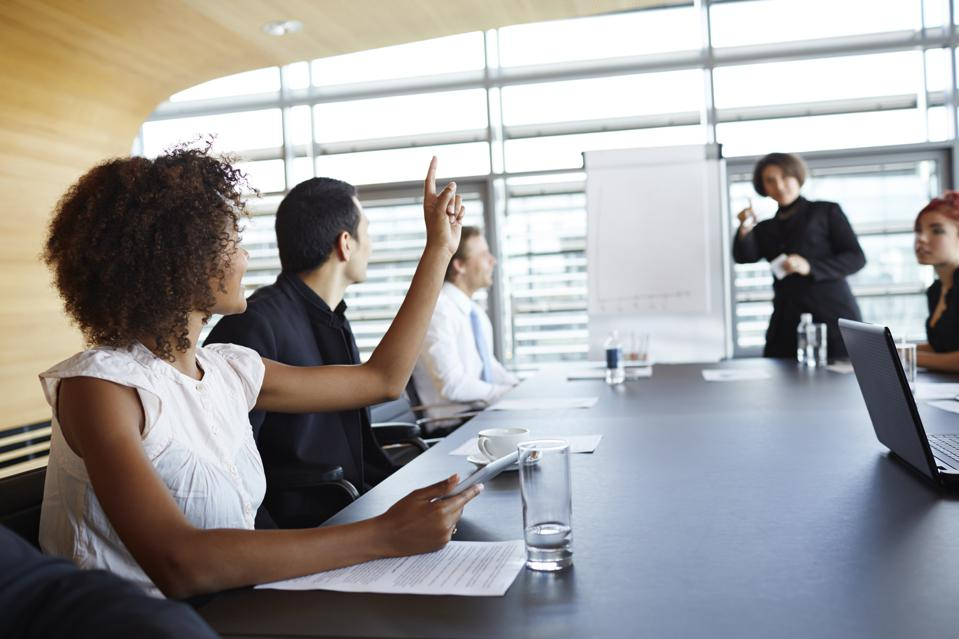 Businesswoman holding up hand at meeting