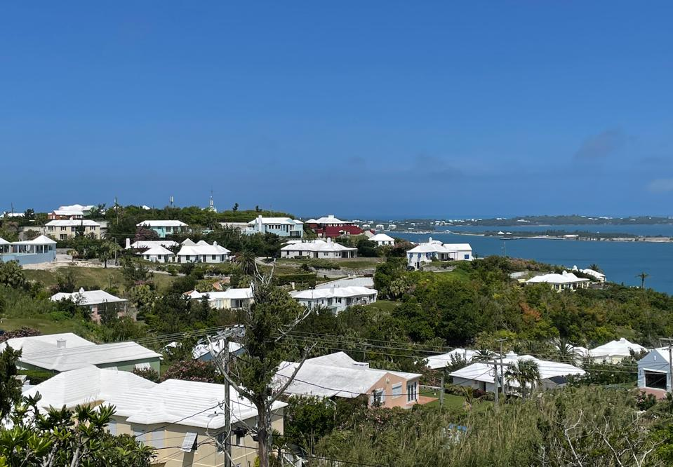 Driving along in Bermuda with pastel cottages and white stepped-roofs