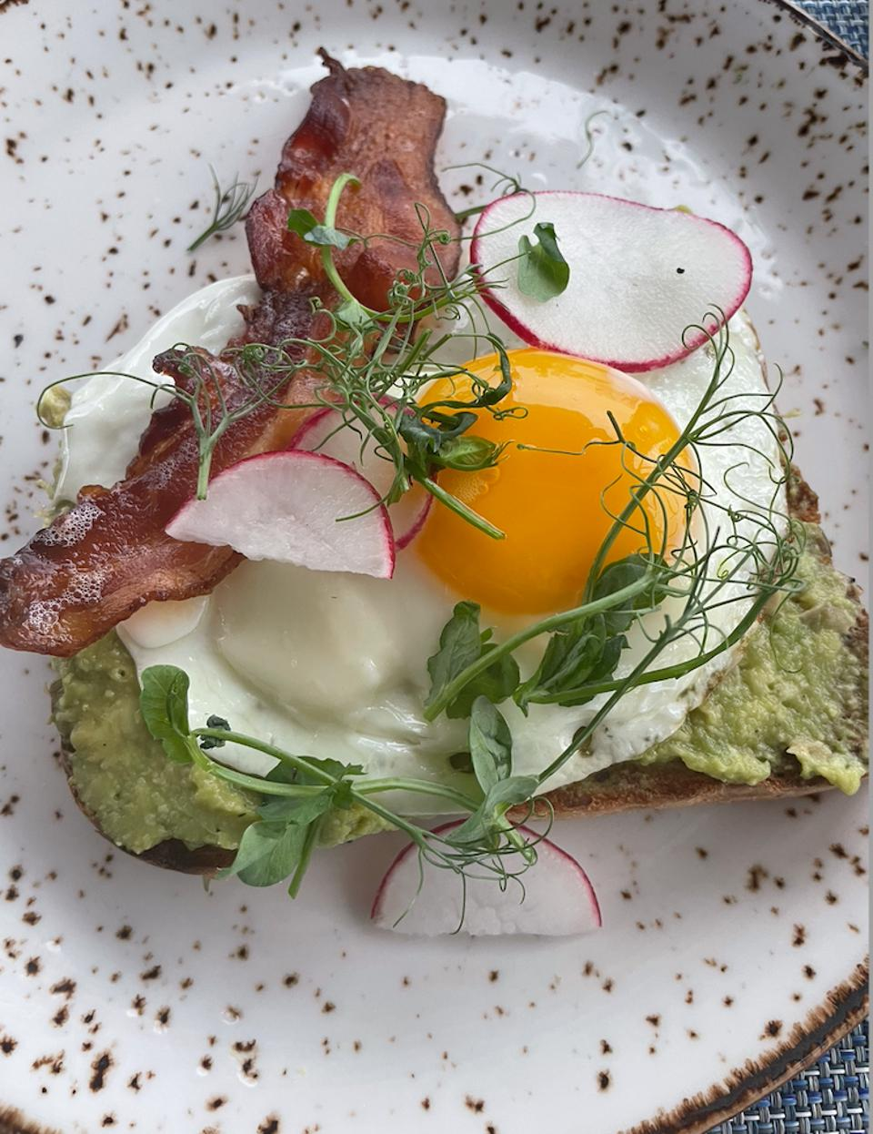 Breakfast at The Loren at Pink Beach: fried egg, avocado toast and Hickory smoked bacon