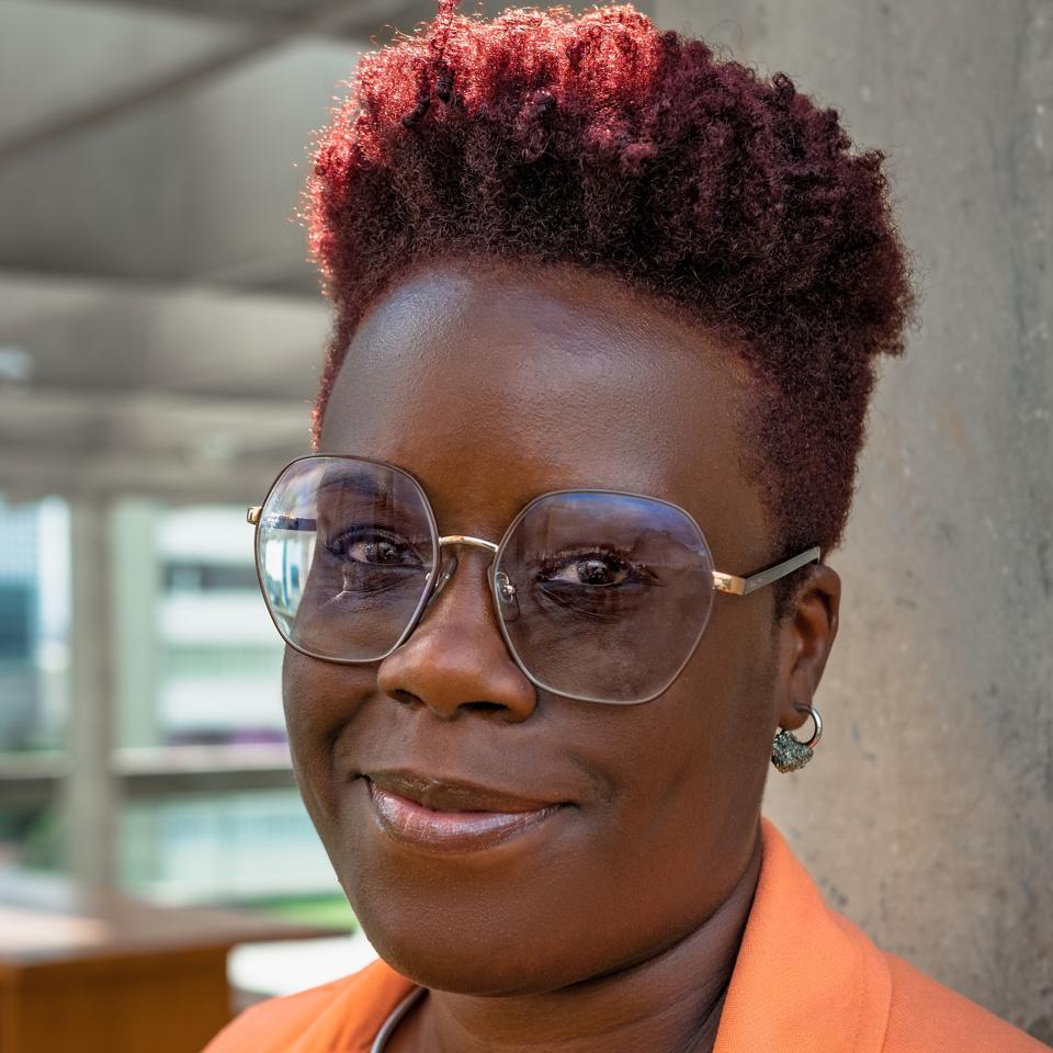 Mita Loreno usa óculos, cabelo curto e uma jaqueta laranja.  Ela é uma mulher negra.
