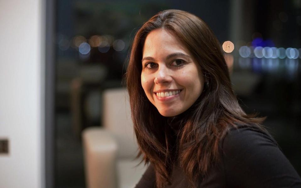 Anita Fiori, usando uma blusa preta e longos cabelos castanhos.  Ela é uma mulher branca.