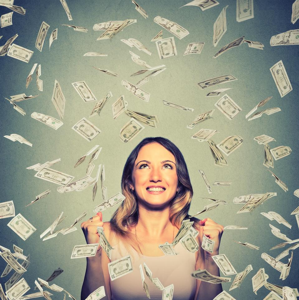 happy woman pumping fists celebrates success under money rain