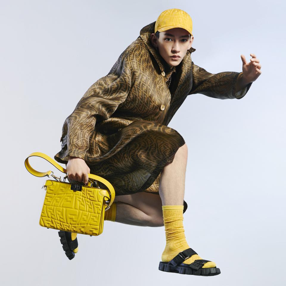 Fendi Summer 2021 Capsule Collection: Model in jumps in trench coat.