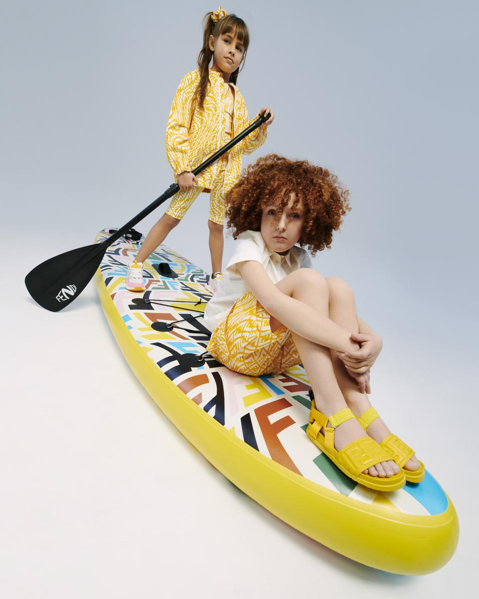 Child models sport the new collection aboard a limited-edition paddleboard.