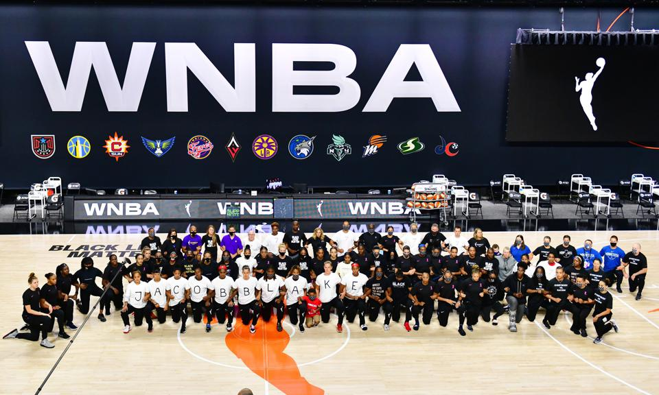 WNBA players kneel on the court to protest the shooting of Jacob Blake.
