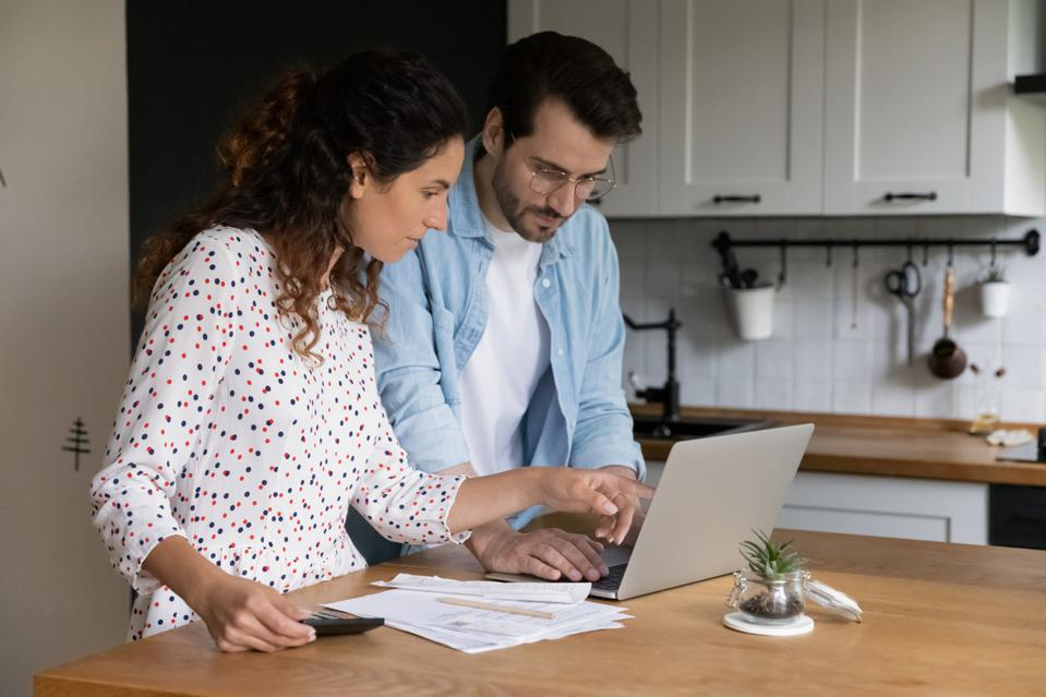 Focused man and woman using laptop, checking financial documents