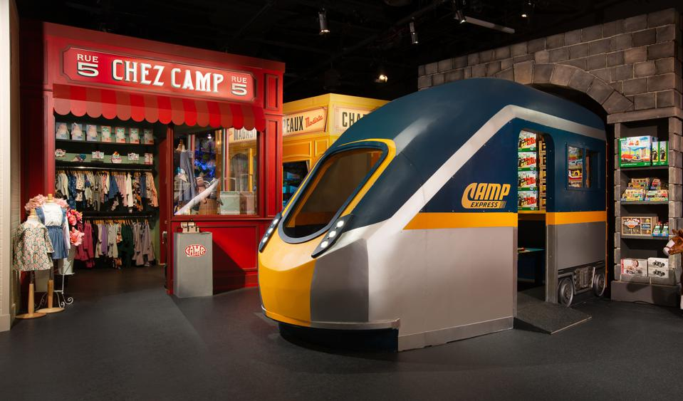 a store display with a train that kids can walk into and a clothing shop that looks like its own store beside it.