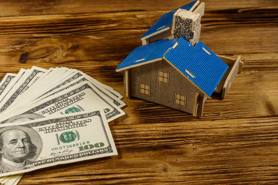 House model and U.S. one hundred dollar bills on wooden background. Property investment, home loan, house mortgage, real estate concept