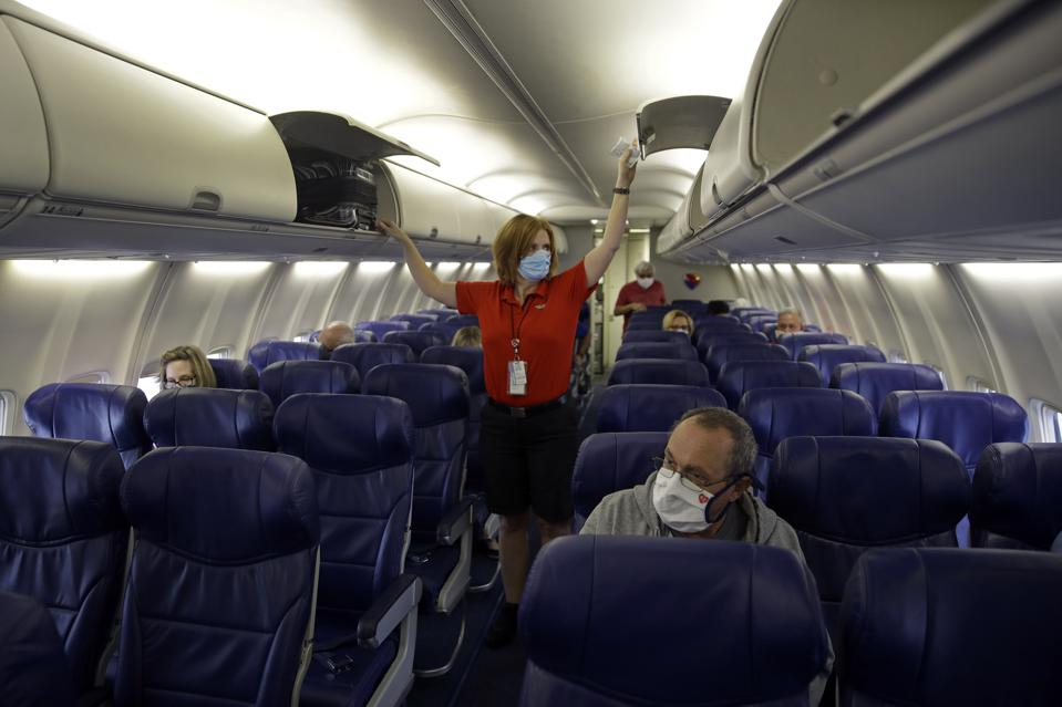 Flight attendant checks overhead compartments on nearly empty aircraft.