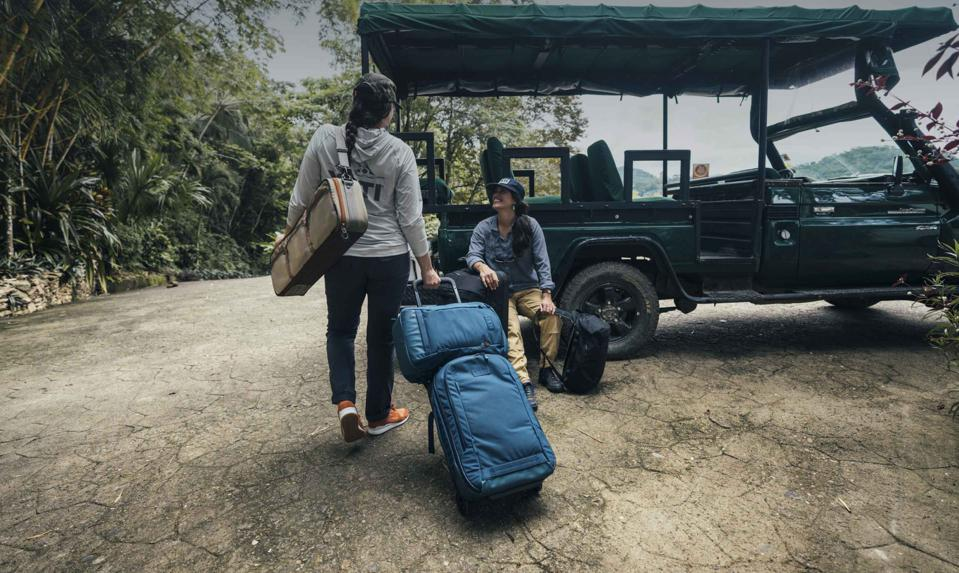 woman pulling luggage towards a person sitting on car YETI