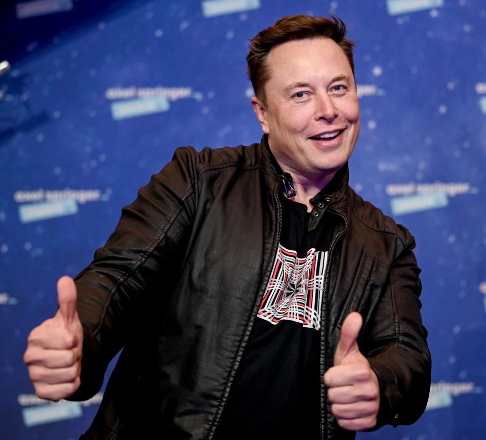 Elon Musk gives photographers a smile and thumbs up in a black leather jacket and tee