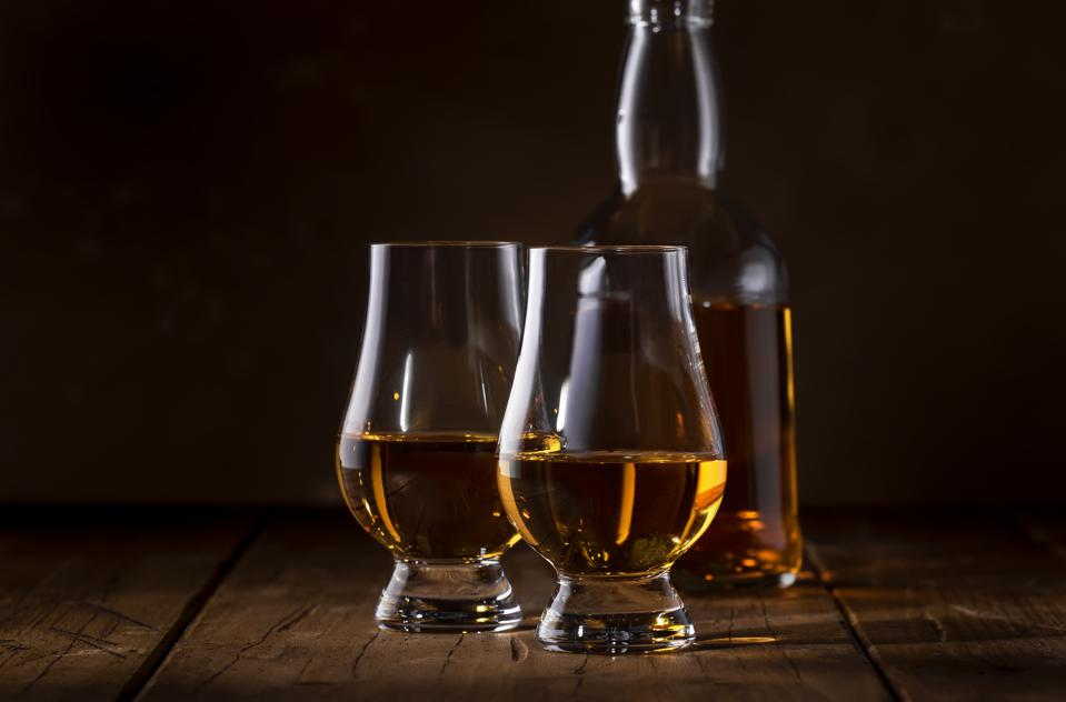 Scotch Whiskey without ice in glasses and bottle, rustic wood background