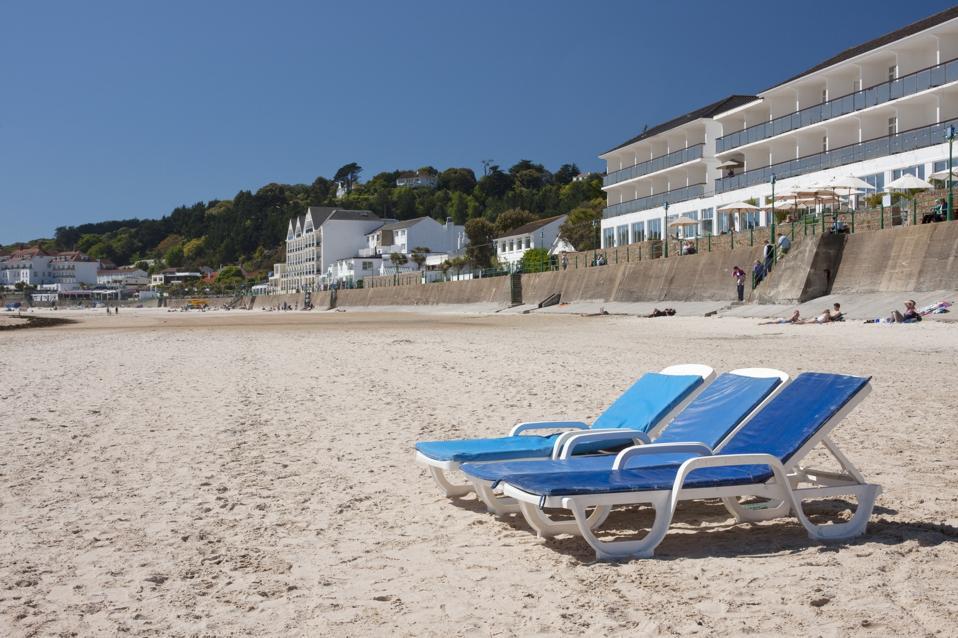 Sun loungers outside Le Horizon, a beach side hotel, St Brelades Beach in Jersey, Channel Islands
