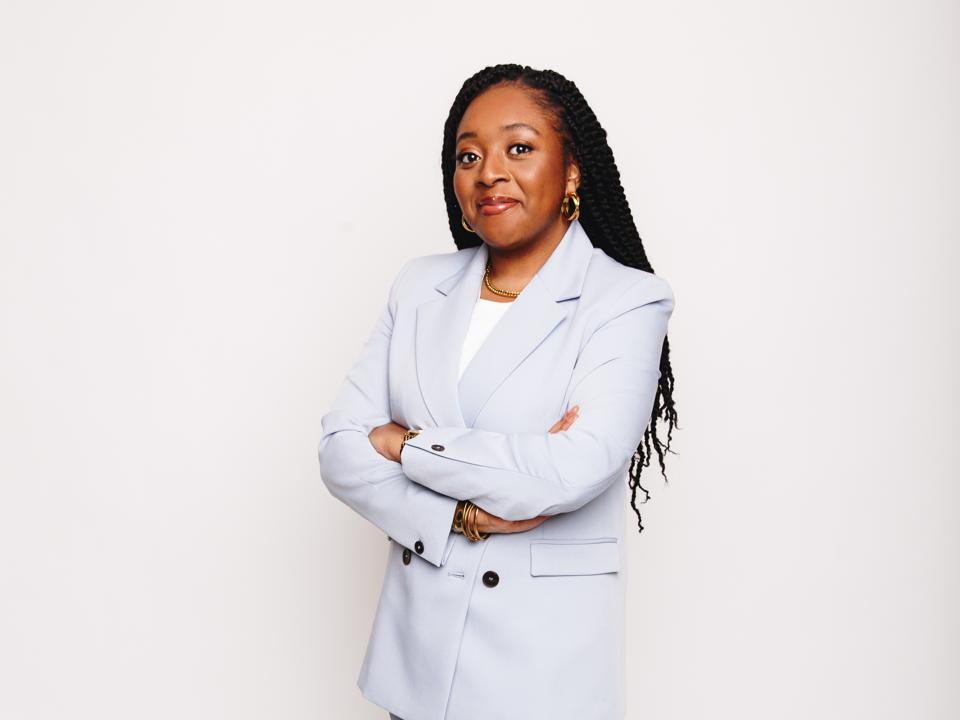 Onyinye Udokporo, Founder of Enrich Learning stands smiling direct to camera, arms folded.
