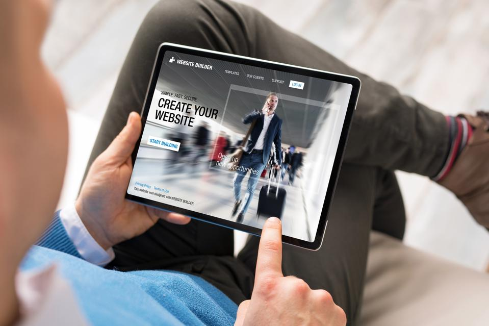 Man creating website for his business by using tablet