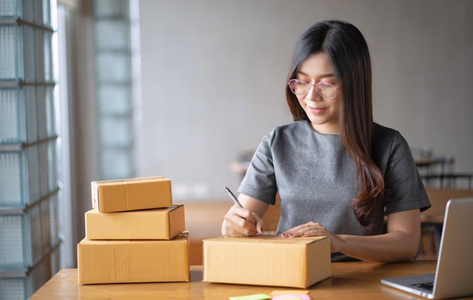 Young business woman working selling online. Entrepreneur owner using Laptop or tablet taking receive and checking online purchase shopping order to preparing pack product box. Online shopping
