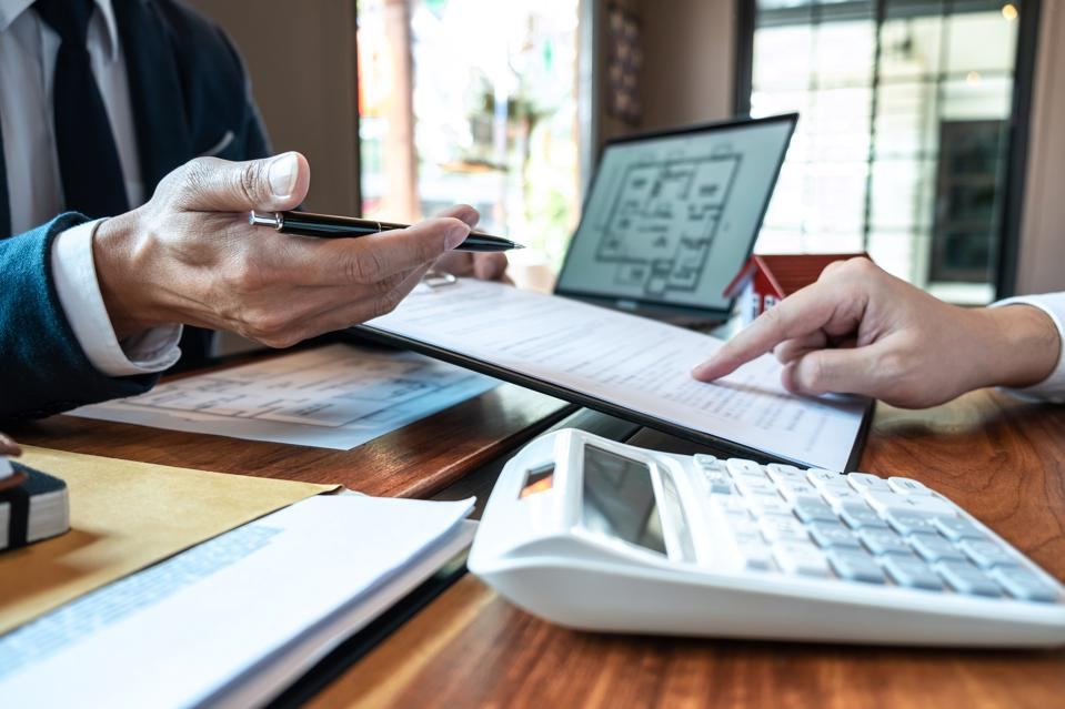 Cropped Hand Of Man Discussing With Real Estate Agent Over Document At Desk