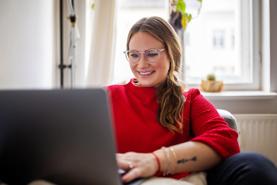 Happy woman working on laptop at home