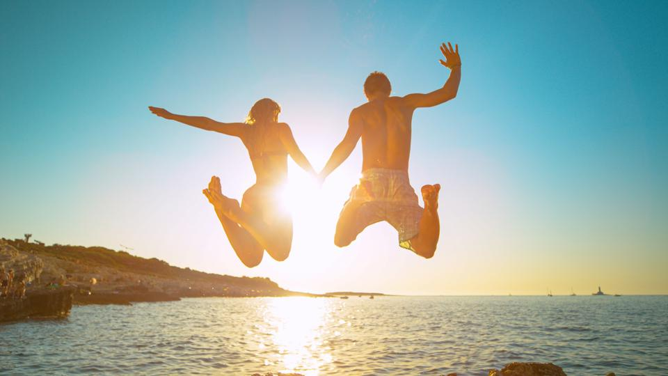 Carefree tourists hold hands while jumping into the refreshing sea