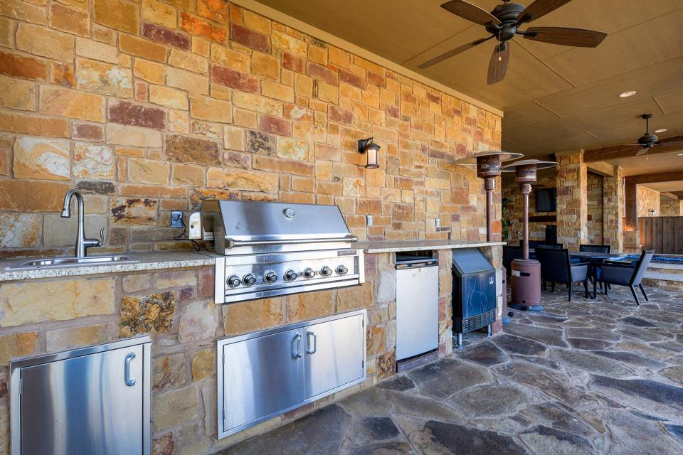An outdoor gourmet kitchen on a patio setting.