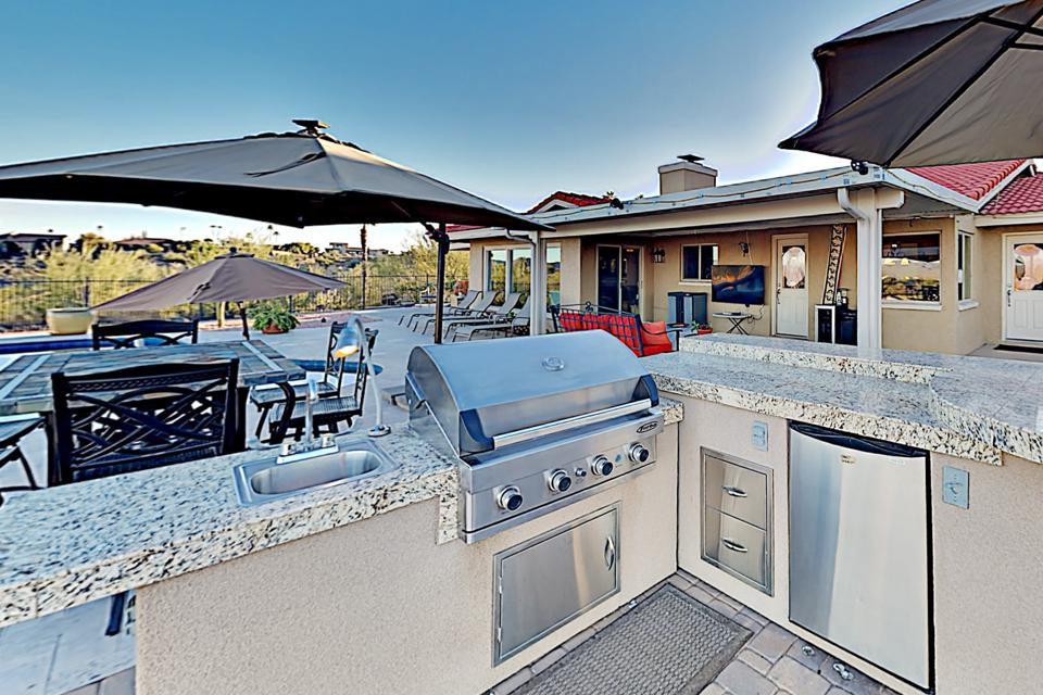 An outdoor grill set and several umbrellas.