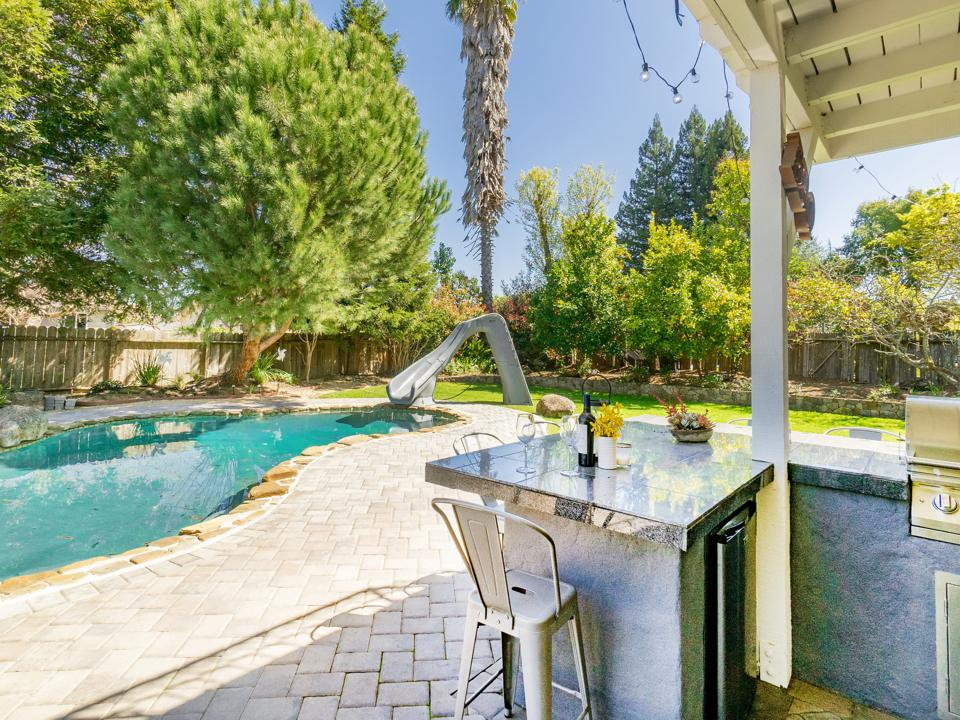 An outdoor pool and large grill.