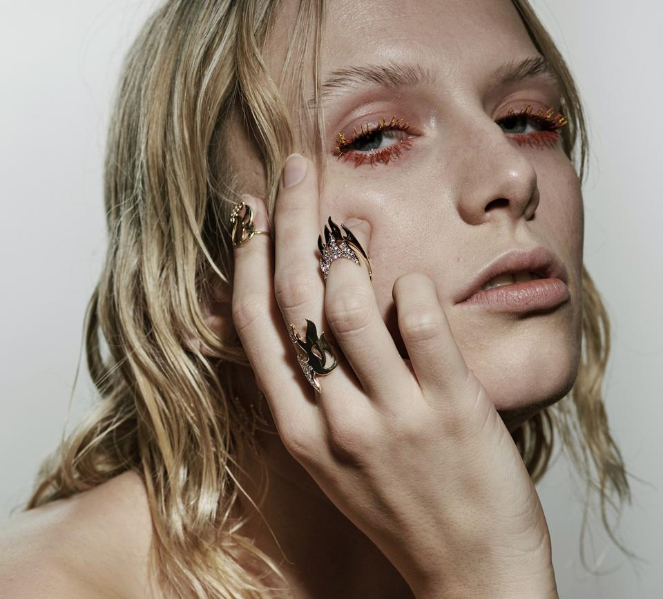 a blond female model wearing gold flame shaped rings