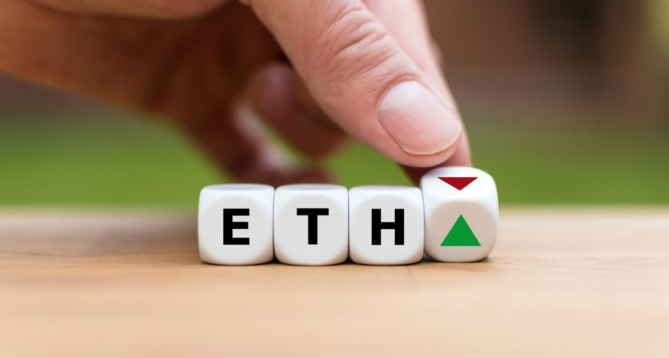 A hand flips over a dice with a red triangle signifying a down trend. Other dice read ETH.