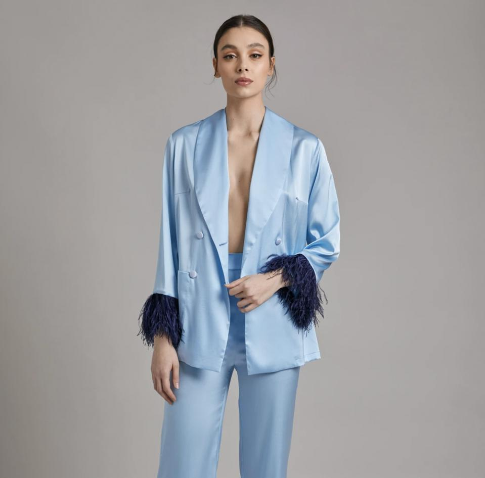 model in blue silk jacket with feathers