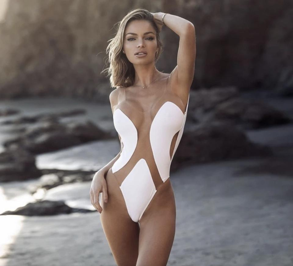 model wearing a white cutout one piece swimsuit