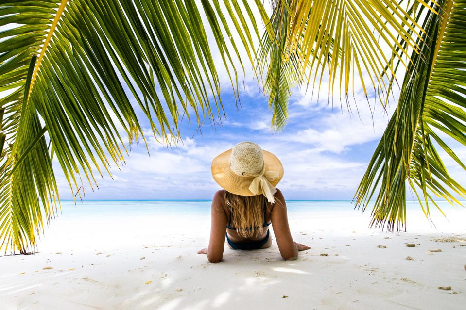 Back view of a woman relaxing in a shadow on the beach.