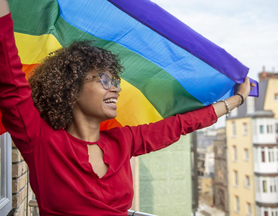 Young lady waving a gay pride flag in support of Gay Pride