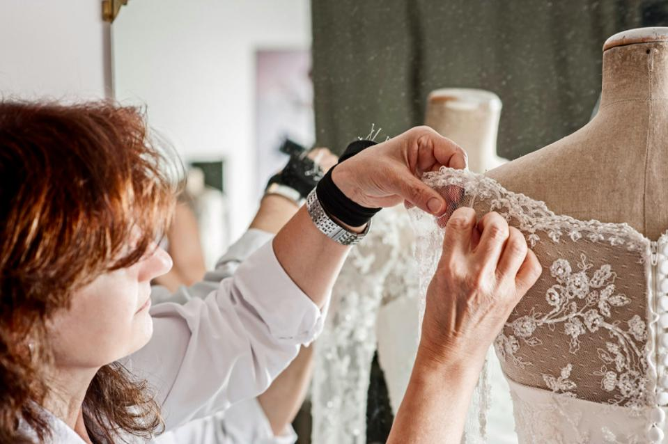 Dress maker and embroiderer working in Cinzia Ferri's atelier on a custom wedding gown