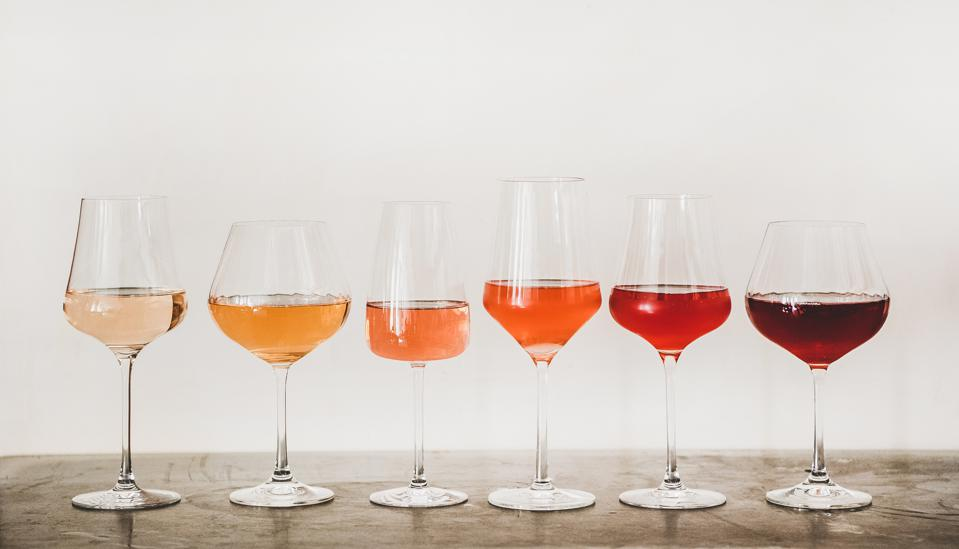 Shades of rosé wine in glasses on concrete table