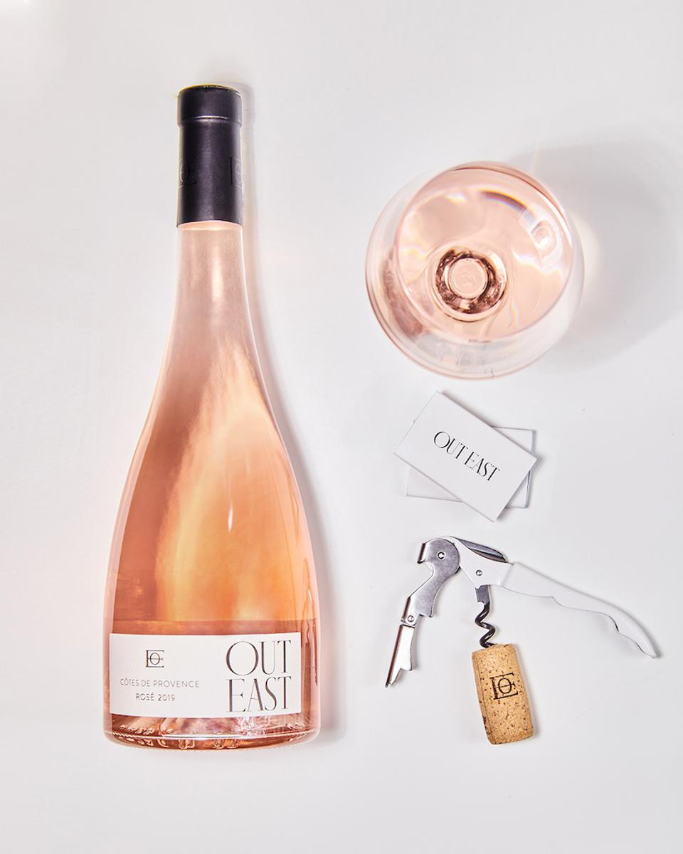 Bottle of Out East Rosé wine with glass and corkscrew against white background