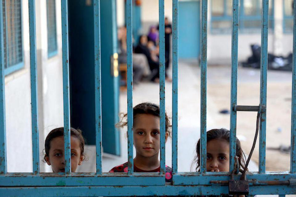 Three girls peek out from behind a gate at one of 29 United Nations Relief and Works Agency for Palestine Refugees schools being used as temporary shelters in the Gaza Strip