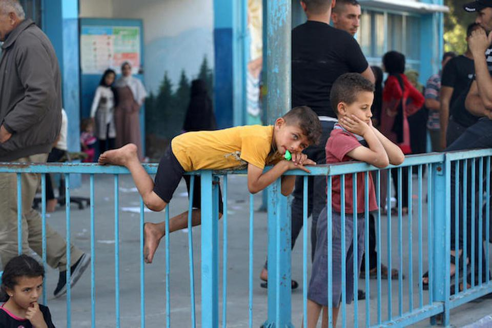 On May 15, 2021, children lean on a fence at a UNRWA school-turned-shelter in Gaza City.