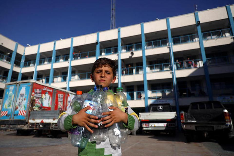 A Palestinian boy holding empty water bottles  looks for a place to fill them with safe drinking water.