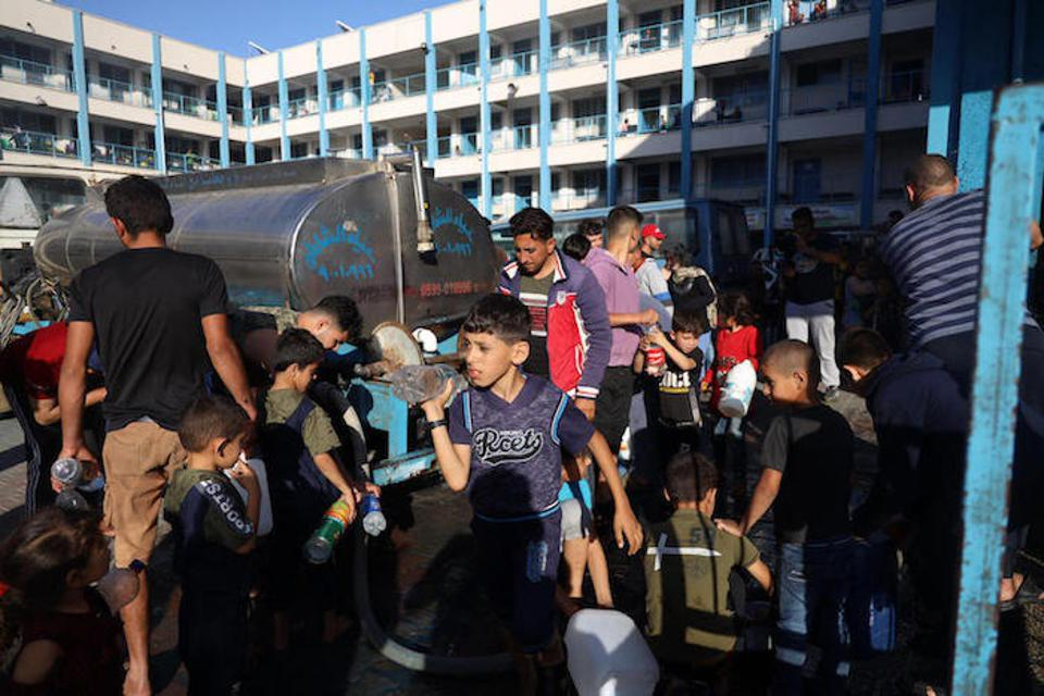 Children gather at a water truck to fill bottles with safe drinking water in Gaza on May 15, 2021.