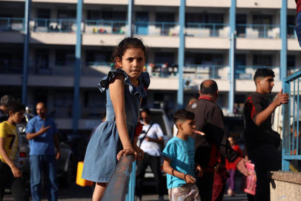 A Palestinian girl stands on metal fence at a school turned shelter for families displaced by bombardment in Gaza.