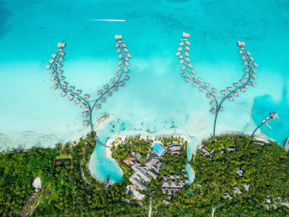 An overhead shot showing two two-branched curved docks with many overwater villas in the pale aquamarine sea. At the bottom of the photo are lush green trees a few hotel buildings and white sand beaches.